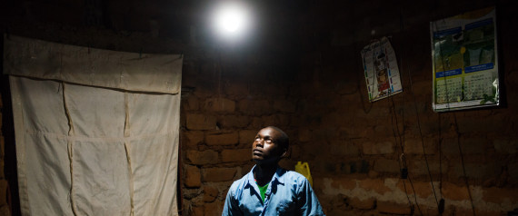 Erasmus Wambua, a schoolboy, looks at a single electric lightbulb, powered by M-Kopa solar technology, as it illuminates his home in Ndela village, Machakos county, in Kenya, on Wednesday, July 22, 2015. Customers agree to pay for the solar panel with regular instalments which M-Kopa, a Nairobi-based provider of solar-lighting systems, then monitors for payments that are made using a mobile-phone money-transfer service. Photographer: Waldo Swiegers/Bloomberg via Getty Images
